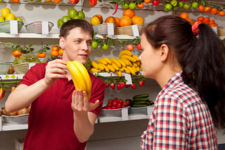 farm shop: Young woman buys banana. Assistant helping customer at vegetable counter of farm shop