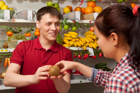 farm shop: Young woman buys kiwi. Assistant helping customer at vegetable counter of farm shop