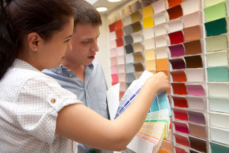 merchandiser: Couple select paint color and look matching samples at household store