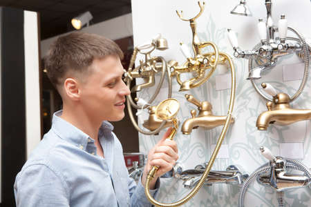 bathroom equipment: Man shopping for bathroom equipment in hardware store, shop for construction