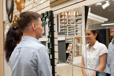removals: Woman and man shopping  in home decoration store looking mirror