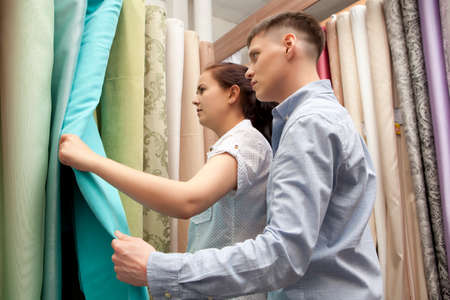 redecoration: Couple buying colorful curtain samples hanging in home decoration store