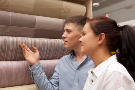 Happy family couple having fun in store choosing for buying wallpaper looking at design image Standard-Bild