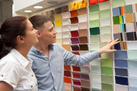 color consultation: Happy couple family select paint color and look matching samples at household store Stock Photo