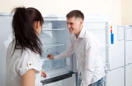 domestic appliances: Happy family couple looking at large fridges in domestic appliances section store