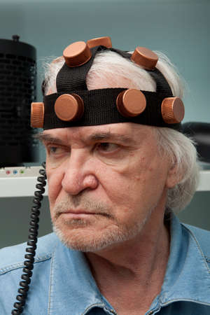 inventor: Aged man crazy inventor wearing a helmet brain research