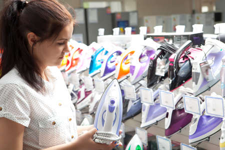 Young woman housewife shopping for iron