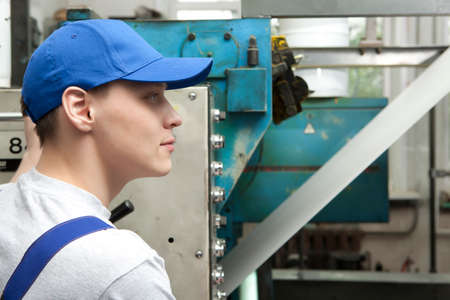 offset printing: Young man in cap working on offset printing machine in print factory