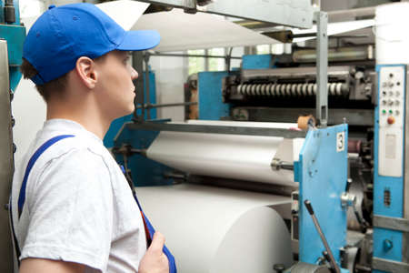 skilled operator: Young man in cap working on offset printing machine in print factory