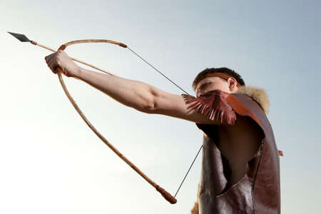skill: Robin Hood. Young archer in vintage clothes with arrow and long bow Stock Photo