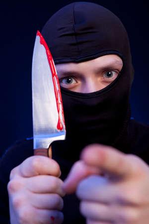 hijacker: Man criminal in black mask with knife over dark blue background