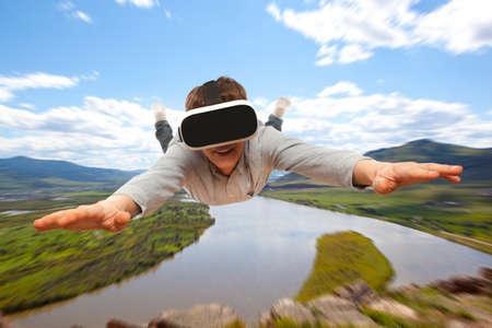 가상 현실 안경을 착용하는 젊은 사람이 자연을 위로 날아