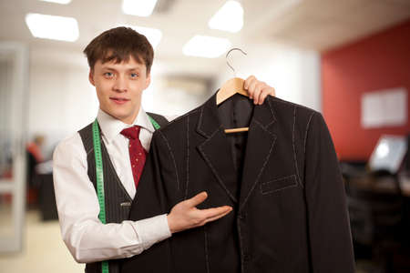 customer tailor: Taylor holds a handmade mans suit