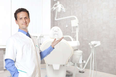 People, medicine, stomatology and healthcare concept - happy male dentist in white coat at dental clinic office photo