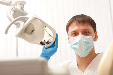 People, medicine, stomatology and healthcare concept - happy male dentist in white coat at dental clinic office