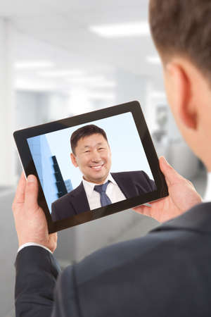 Cropped image of asian businessman attending video conference with colleague on digital tablet photo
