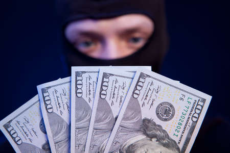 Robber holding money isolated on dark blue background Stock Photo