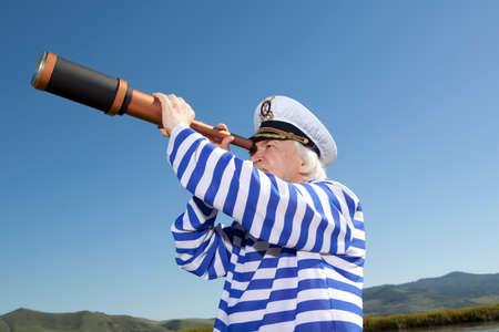 horizon: Captain looks through a telescope. Marine concept