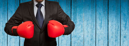 padding: Businessman in red boxing gloves on blue wooden wall background