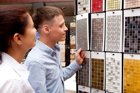 sale shop: Couple pointing at ceramic mosaic tile for bathroom wall in store, in home improvement warehouse exterior Stock Photo