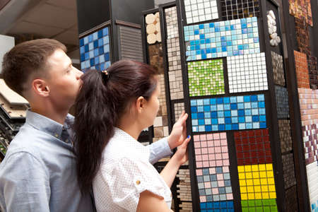 Couple pointing at ceramic mosaic tile for bathroom wall in store, in home improvement warehouse exterior Archivio Fotografico
