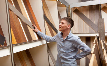 wenge: Men looking at parquet board for home flooring in store, in home improvement warehouse exterior Stock Photo