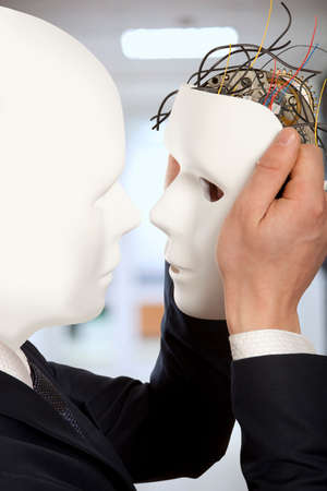 Cyborg, clone, robot and artificial man concept - Businessmen android robot holds clone white face mask Stock Photo