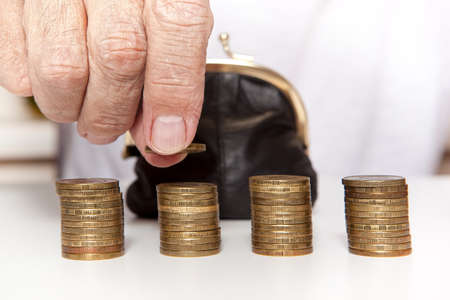 destitution: Old senior hands holding coin and small retro styled money pouch