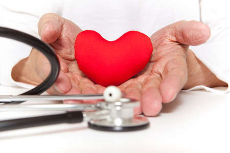Arterial blood pressure, health and medicine concept - old hands of the elderly giving a red heart Stock Photo