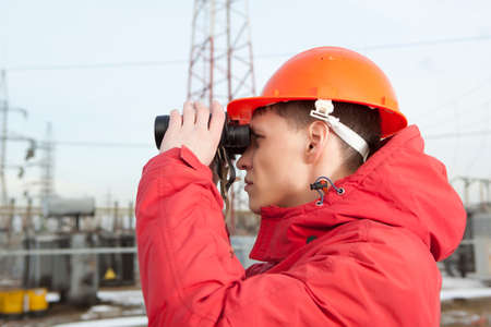 power industry: Engineer at Electrical Substation looks through a binoculars. Electrical power industry