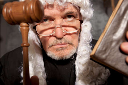 Judge. Senior judge in a courtroom striking the gavel Stock Photo
