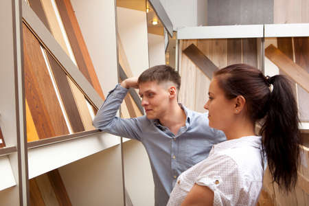 Couple looking at parquet board for home flooring in store, in home improvement warehouse exterior Stock Photo