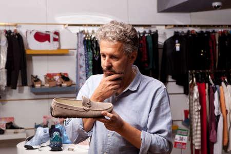 choosing clothes: Adult man choosing shoes during footwear shopping at shoe shop Stock Photo