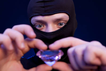 Thief. Man in black mask with a big emerald over dark blue background Stock Photo