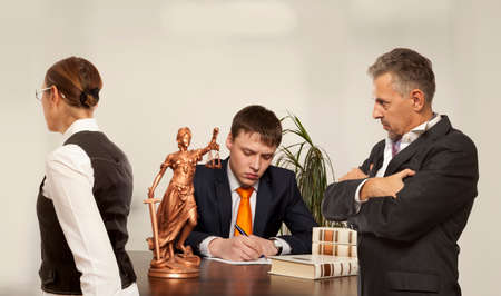 Couple with judge writing at desk in court. Divorcement concept Stock Photo