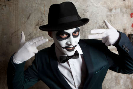Evil clown: Scary evil clown wearing a bowler hat on wall background Stock Photo