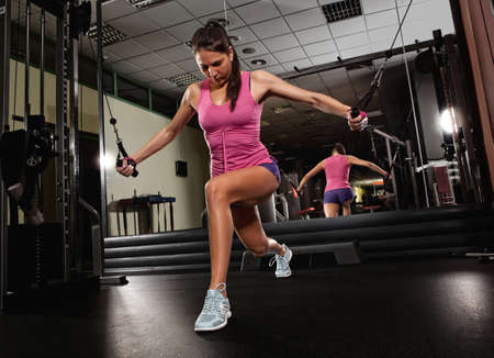 Fitness woman execute exercise with exercise-machine Cable crossover in gym Stock Photo