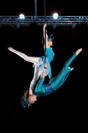 Young couple circus air gymnast. On black background