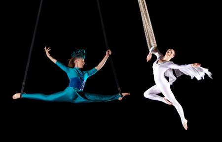 若いカップル、サーカス空気体操です。黒い背景に 写真素材