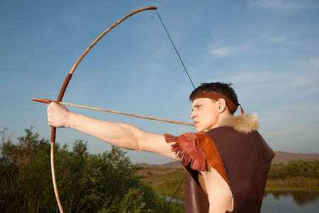 weapons: Robin Hood. Young archer in vintage clothes with arrow and long bow Stock Photo