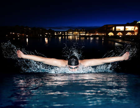 Young man in black cap in swimming pool. Butterfly style Stock Photo