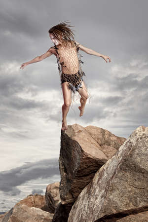 recluse: Wild man stands on a rock on grey sky background