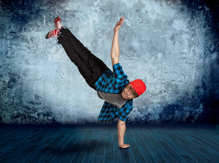 Young man break dancing on wall background Stock Photo
