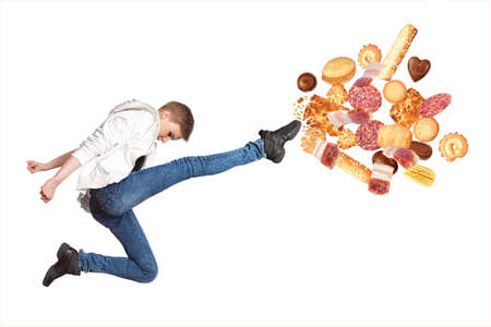 Fit young woman fighting off bad food isolation on a white background Stock Photo