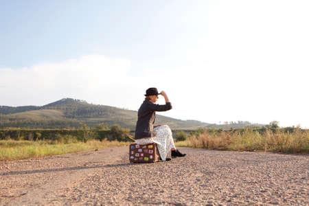 Vrouwen met vintage reiskoffer op oude weg