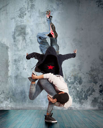 Two young man break dancing on wall background
