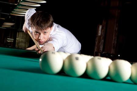 Young man playing billiards in the dark billiard club Stock Photo
