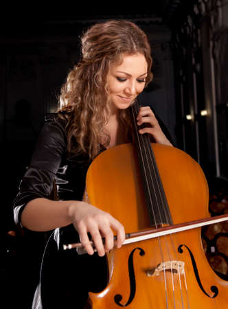 Musician play cello on dark background