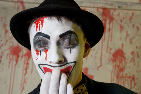 Scary evil clown wearing a bowler hat on wall background Stock Photo