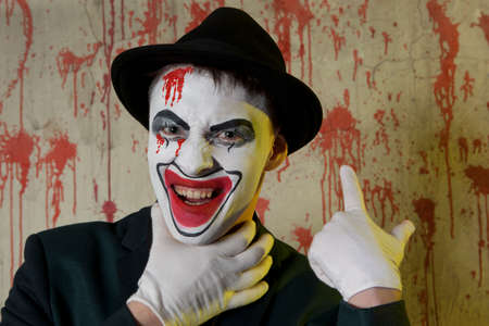 suffocate: Evil clown hands by the throat on a wall background, suffocation, choking